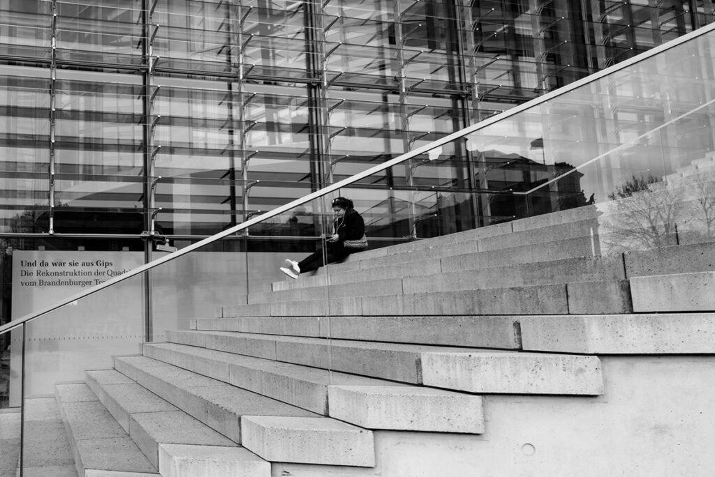 Leica Q2: Eine Frau sitzt im Berliner Regierungsviertel auf der Treppe